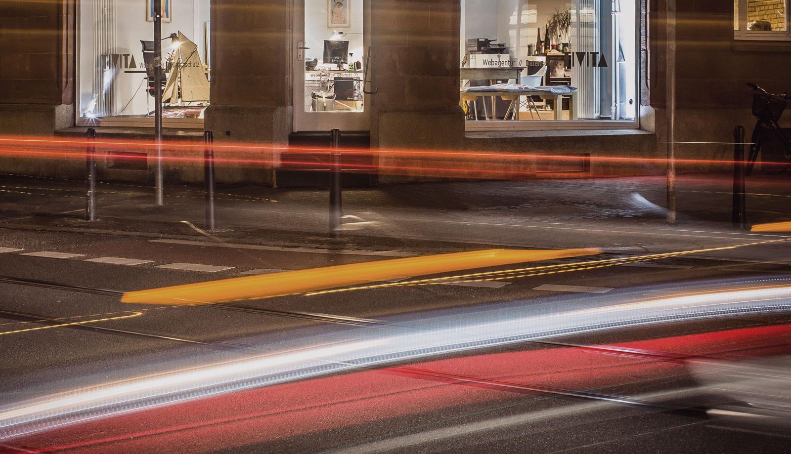 Die Büroräume der TIVITA GmbH von außen mit Lichtstreifen vorbei fahrender Autos